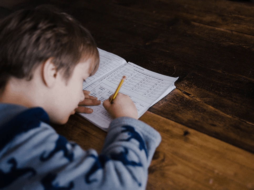 Child Holding Hands Up Surrounded By Learning Materials