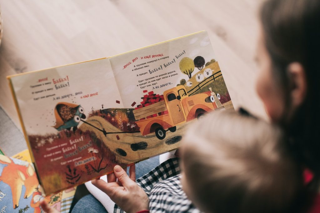 woman reading book to her child